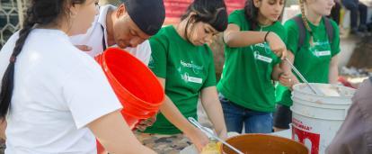 Voluntarios de apoyo a los refugiados sirviendo comida durante su proyecto.